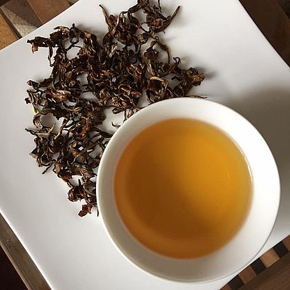 """Ancient Snow Shan Tra Pai Hao """"Red"""" Tea, served with view on the infusion"""