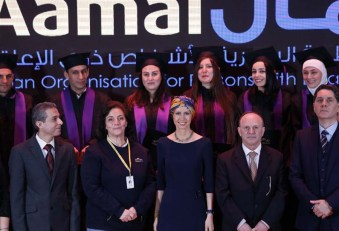 Syria's First Lady Asma al-Assad (bottom C) participates in a graduation ceremony of future teachers of a Syrian Organisation for Persons with Disabilities, in Damascus on December 3, 2018. - The Syrian president's wife is currently undergoing treatment for breast cancer, the presidency said earlier this year. (Photo by LOUAI BESHARA / AFP)