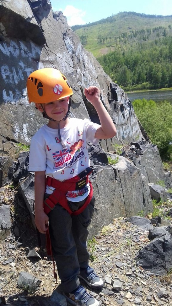 boy poses in climbing helmet and harness in green hilly setting with cliffs