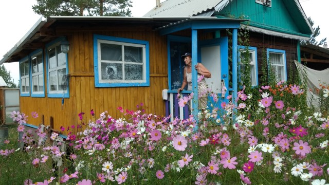 woman at the entrance to a small house with cosmos flowers in front