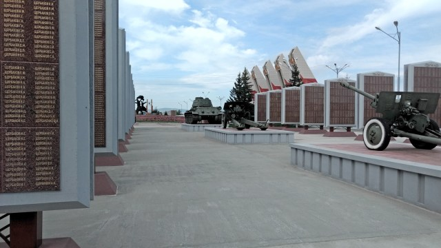 rows of panels with names of the war dead, two cannons and the cnetral statute and columns in the distance