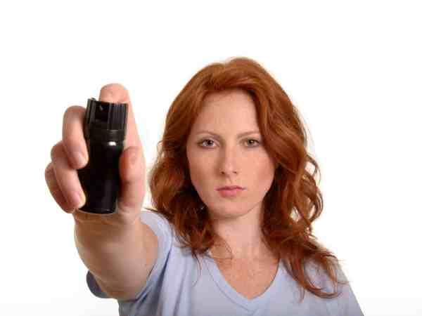 Frau hält Pfefferspray in der rechten Hand