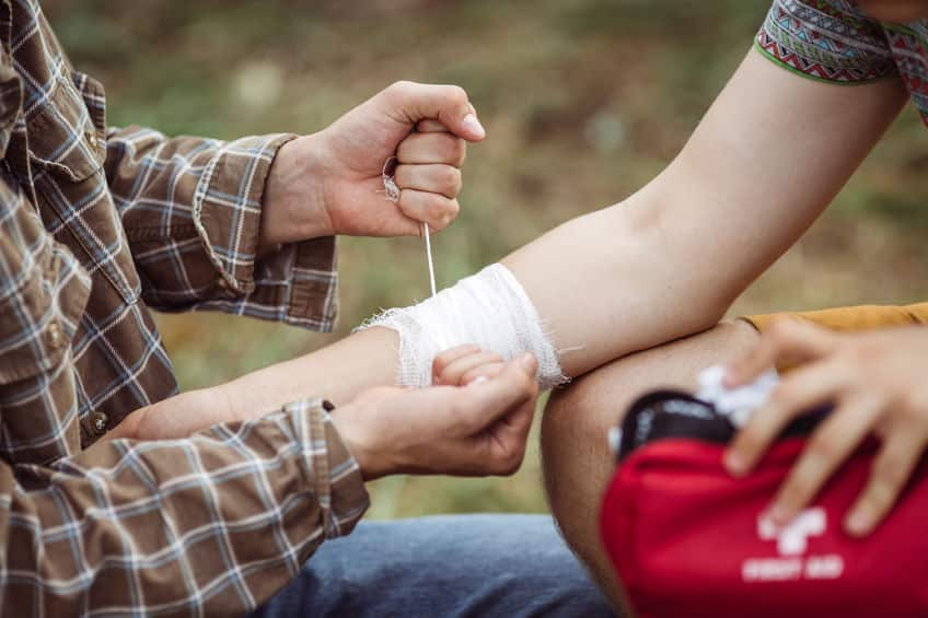 42656900 – a person wrapping his friends injured arm in gauze
