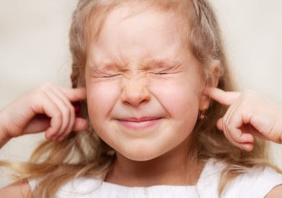 Child with autism plugging her hears and shutting her eyes tight.