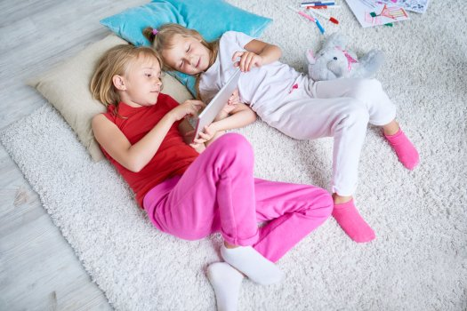 Two young girls laying on the carpet looking at an iPad together.