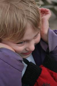 Child with sensory processing disorder covering ears and smiling while playing outside.