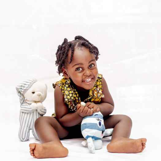 Black toddler smiling playing with toys in a white room during an early autism diagnosis.