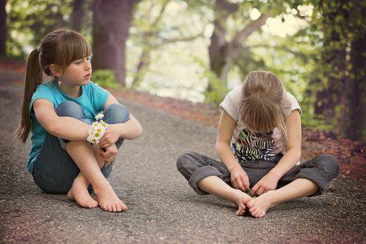 Two girls engaging in social communication, sitting on the ground in a forested area.