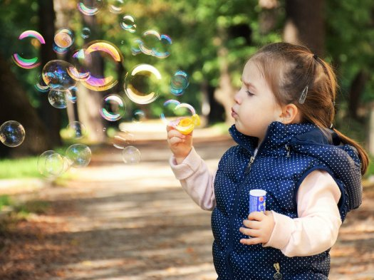 Toddler blowing bubbles. Should her parents try to cure her autism?