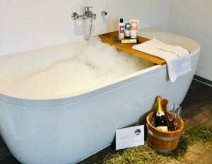 Buurehofwellness - Badewanne mit Sidefyn Produkten und einer Flasche Sekt