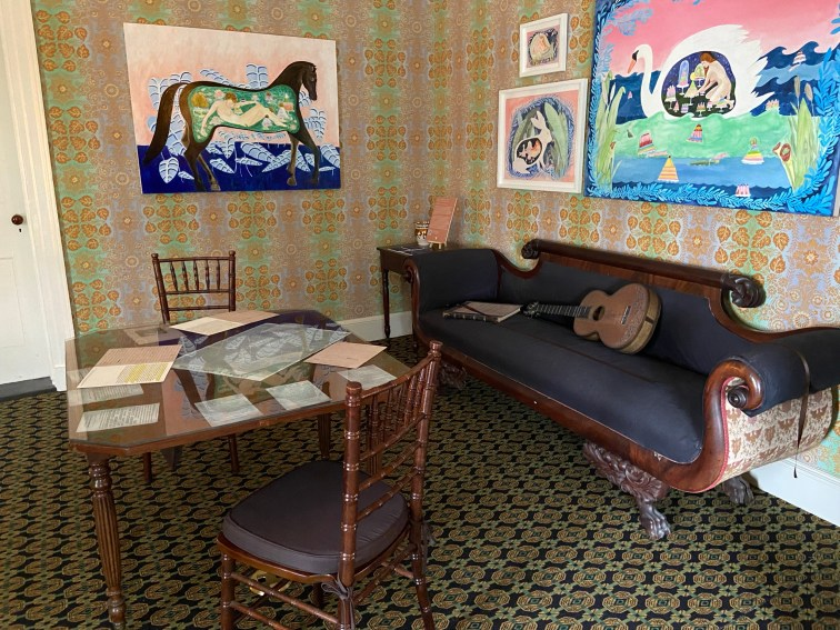 """The second-floor sitting room of the Main House is decorated with a re-creation of the vibrant original wallpaper. Works by Dana Sherwood, such as Inside the Belly of a Horse, are part of the """"Cross Pollination"""" exhibition."""