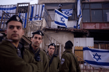 Israeli Border Police officers look on during a protest against the eviction of Palestinians from their homes by Israeli settlers in the East Jerusalem neighborhood of Sheikh Jarrah,December 25, 2009