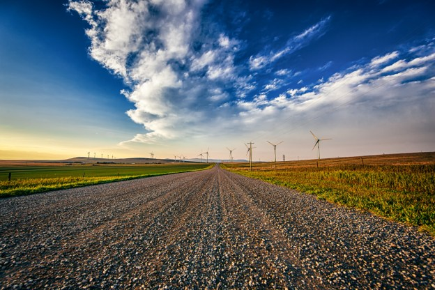 Pincher Creek wind farm with a gravel dirt road down the middle during a late summer sunset against a Canadian Rockies backdrop, Alberta landscape, copy space, horizontal.