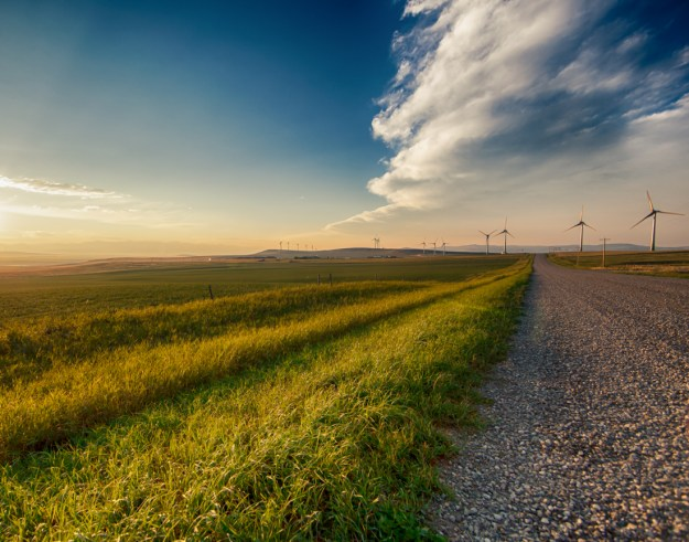 Pincher Creek windfarm during the sunset along a gravel dirt road-Alberta landscape.