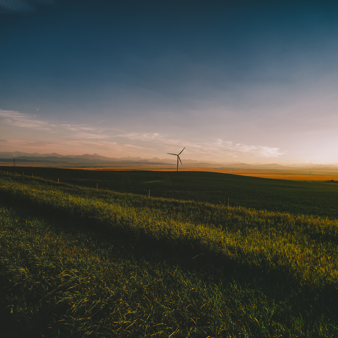 Wind turbine operates against a Canadian Rockies backdrop during a late summer sunset near Pincher Creek. Alberta landscape. Copy space horizontal.