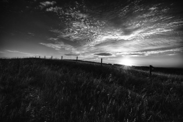 Black and white Southern rural Alberta sunrise over the Canadian Rockies and neighbouring farmland with wire fence and wooden fenceposts. Alberta landscape.