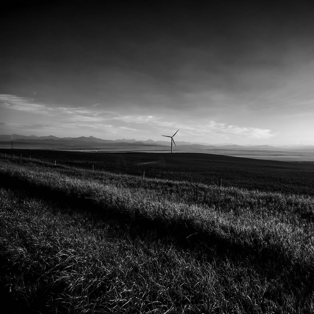 Black and white wind turbine operates against a Canadian Rockies backdrop during a late summer sunset near Pincher Creek. Alberta landscape.