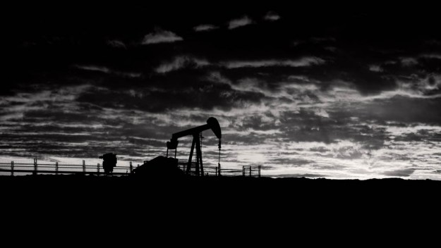 Working pumpjack during a mid-winter sunrise, black and white fine art oil and gas rural Alberta landscape.