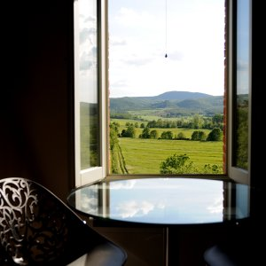 image of a Tuscan view with rolling hills viewed through a window of a room the blue sky with fluffy clouds reflected in the glass table top it's the lounge room of the montepulciano suite at siena house tuscany