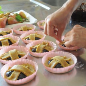 image of the making of a Tuscan crostata or jam tart showing hands assembling the lattice in pastry on the top of the tart in the form of a cross