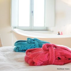 Image of two bath robes in pink and cyan on a bed with a large free standing bath tub behind