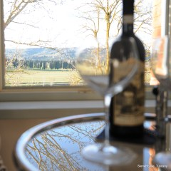 Image of a bottle of vino nobile di montepulciano on a table in a view with wine glasses glass table reflecting the branches of trees and the sky