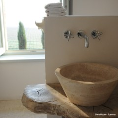Image of a stone vessel sink and chainsaw cut oak shelf in the Cortona bathroom at Siena House