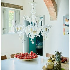 Image showing murano chandelier in clear glass haning over a gervasoni table in a modernised tuscan farm house