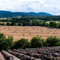 Image showing tuscan countyside in high summer the fields are viewed from inside the viewing tower of the leopoldina luxury modernised farm house villa property in Siena the boutique hotel and holiday home siena house tuscany showing mountains in the background in blues and in the foreground hay bales in the fields