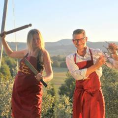 image showing two honeymooners playing having fun with tuscan cooking at the villa bed and breakfast they are staying at showing rolling hills view in the background