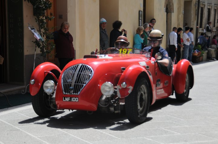 Image showing a red vintage racing car driving through the centre of a Sienese town in Springtime the mille miglia passes though siena and arezzo