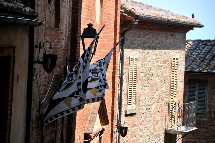 Image showing a red brick Sienese hill town wall with contrada flags in the foreground and terracotta roof tiles in the back ground