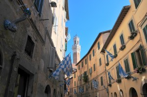 image showing the Piazza il campo tower in Siena, as viewed from one of the medieval side streets the ochre walls of the houses and the green painted shutters with blue and white contrada flags flying