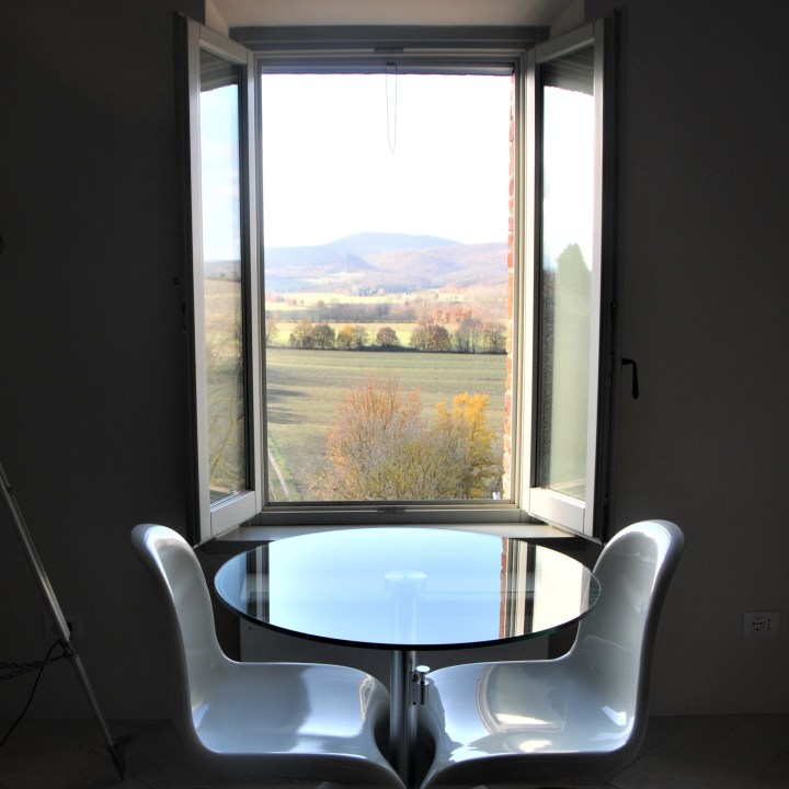 image showing a a table in front of a window, glass round table top two white phantom chairs the view through the window is tuscan hills and countryside this is the montepulciano suite at siena house boutique hotel in tuscany