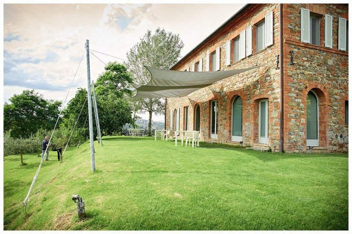 Image showing a tuscan farmhouse in red brick with large windows on top of a grassy hill with pastel woodwork this is siena house boutique hotel in tuscany