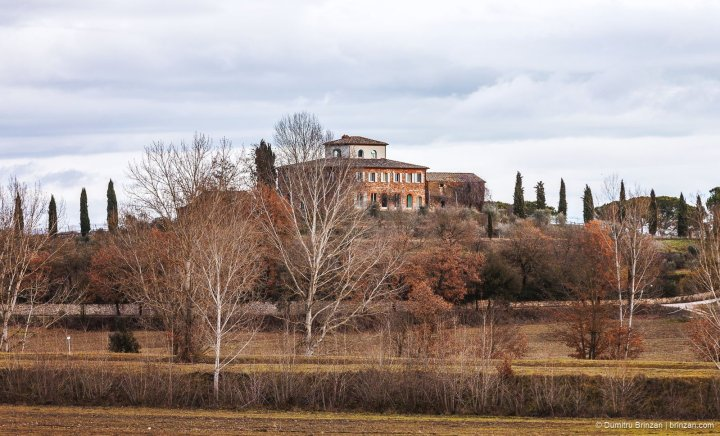 Image showing a boutique hotel in Tuscany leopoldina farmhouse built in red brick on a small hill or poggio totally surrounded by a wall at the base of the hill cypress tree lined drive square house in red brick with white tower and many trees in the garden tuscany in winter photo with grey sky and winter trees siena colour terracotta