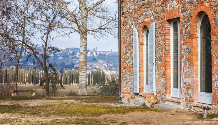 Image showing winter landscape views of and from the garden of siena house a red brick burnt sienna and pietra serena leopoldina with baby blue windows and doors cypress trees line the drive to the boutique hotel in the mid distance and in the background a hill town showing tower and building in the town square atop a hill