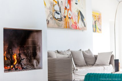 image showing the white interior of a tuscan country house with fireplace lit in the foreground taupe sofa and art above painting by amanda helen atkins on the wall