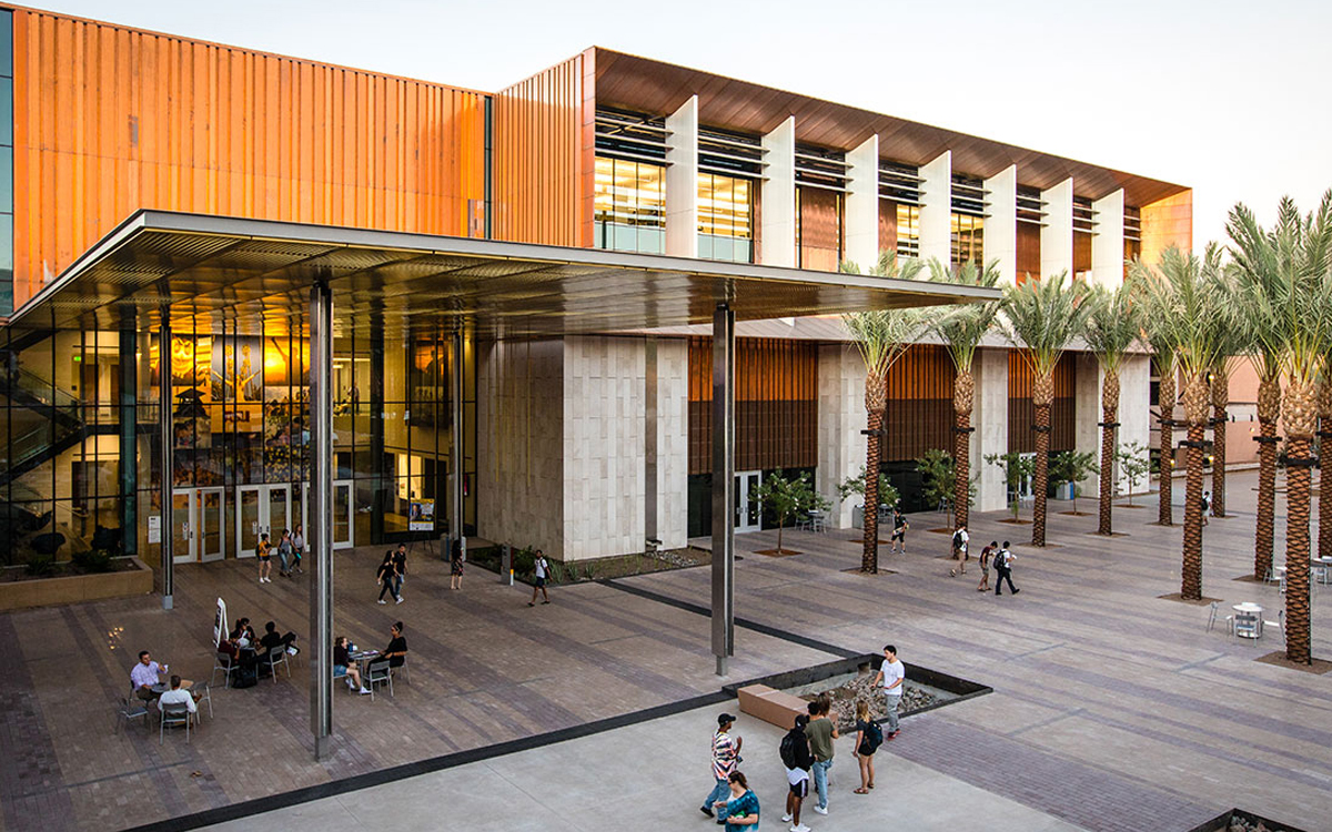 A modern-looking building is fronted by a large brick patio and palm trees.
