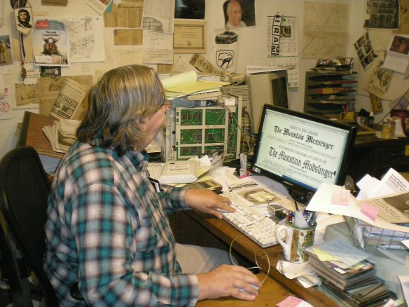 Mountain Man (note plaid shirt) Editor Don Russell stares at computer screen wondering how the Messenger appeared before him and what to do next...