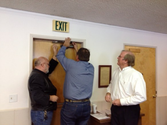 Supervisor Paul Roen tries to fix a stubborn stuck door at the Loyalton Center while Supervisor Peter Huebner helps and Tim Beals directs...
