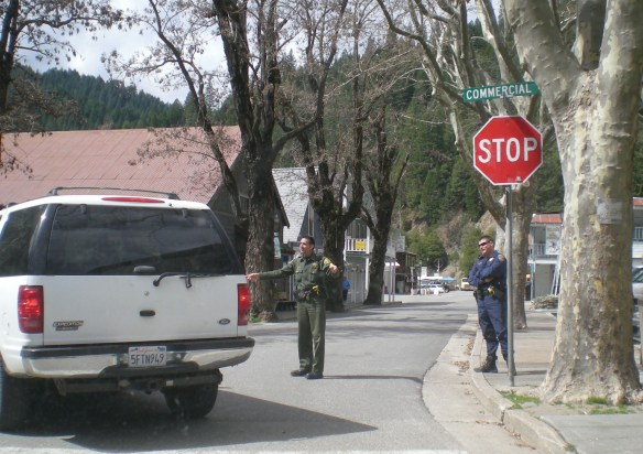 Sgt Tim Standley directs traffic at Stop sign in Downieville as CHP Officer Zack Zostic supervises.