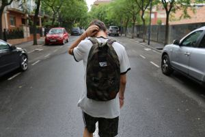 back of teen boy walking down street backpack hand on head