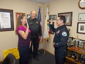 Town Clerk Jamie Gray swears in new MLPD Officer Jack Loera.  Chief Watson looks on.