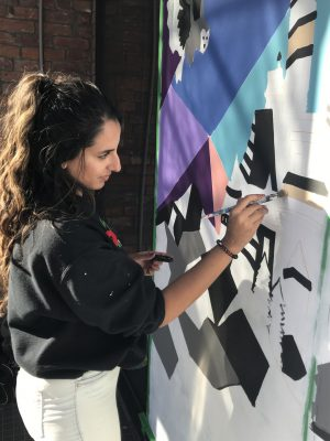 Toronto-based artist Jasmin Pannu painting a storefront window in The Junction for the Window Wonderland exhibition, the city's first augmented reality outdoor art exhibition.