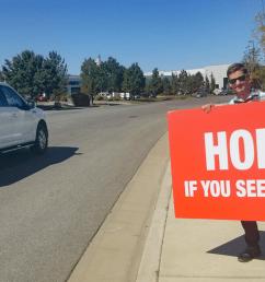 man holding sign on roadside  [ 1563 x 810 Pixel ]