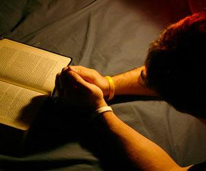 Joven orando de rodillas junto a la Biblia