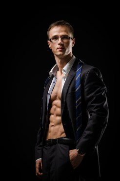 Man in suit with his shirt unbottoned to show off his fit body