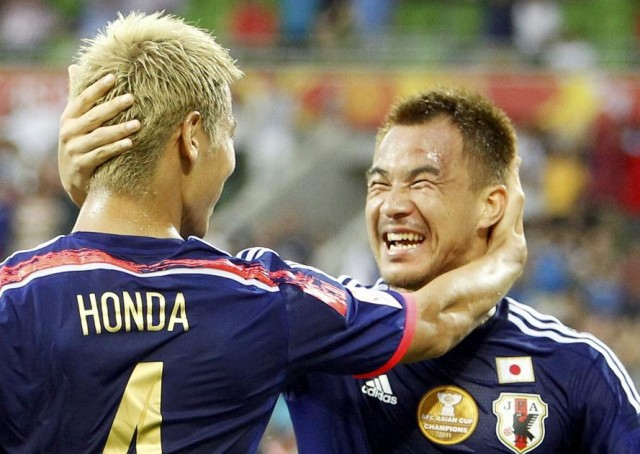 Japan's Keisuke Honda celebrates with teammate Shinji Okazaki after scoring a goal against Jordan during their Asian Cup Group D soccer match at the Rectangular stadium in Melbourne