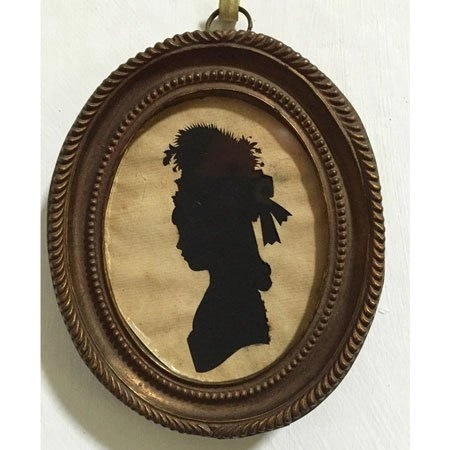 Silhouette of a young girl with floral hat in an oval frame, by Sarah Harrington